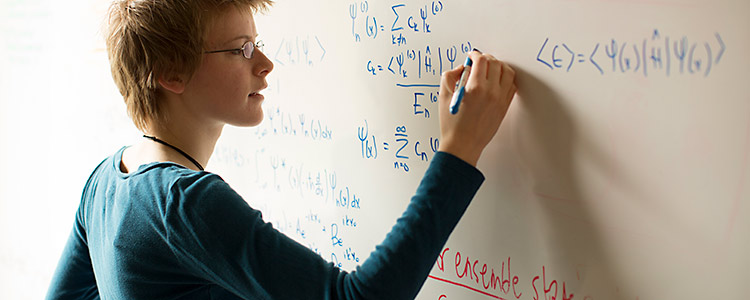 Female mathematical physics student writes formulas on white board.