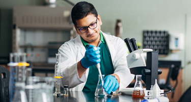 Student wearing a lab coat using a pipette