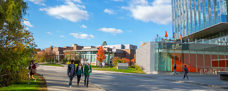Students walking past modern glass building at the University of Waterloo