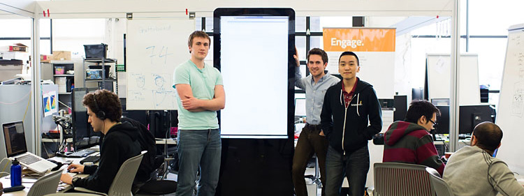 Students standing in front of large display screen in cluttered business incubator