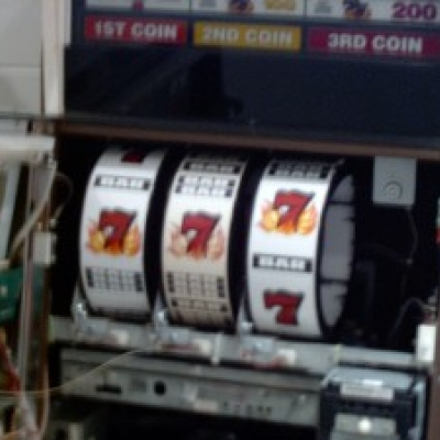 Open slot machine showing the reels with three blazing 7's.