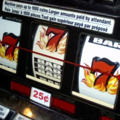 The reel of a Blazing 7's slot machine showing a 7, in between a 7 and a bar, and another 7..