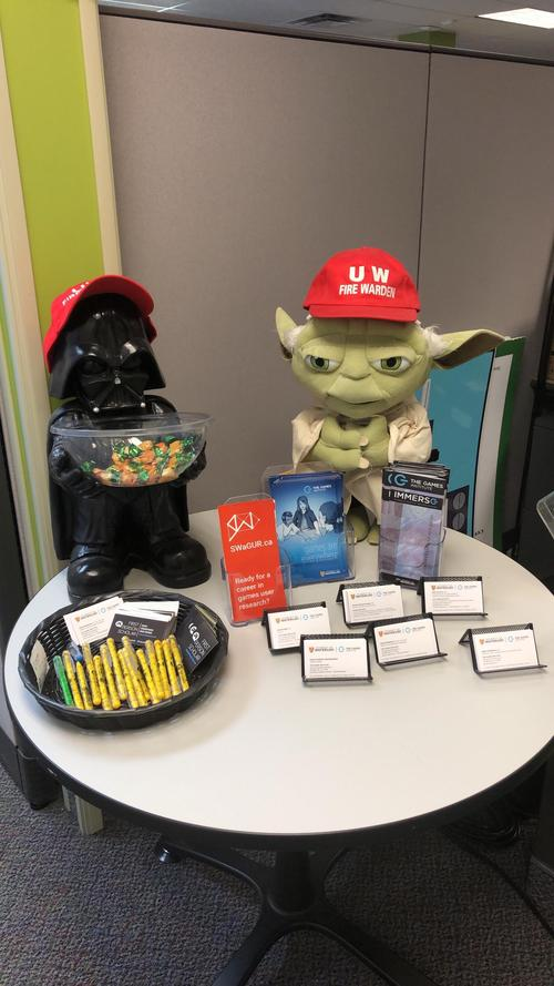 Darth Vader and Yoda sitting on welcome desk with pens and business cards