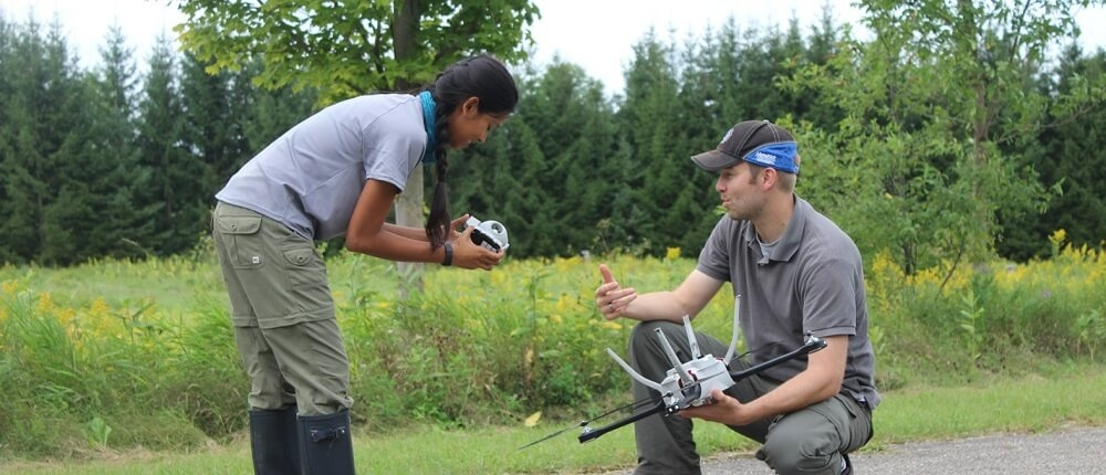 Professor Derek Robinson and a student replacing battery cell on a drone.
