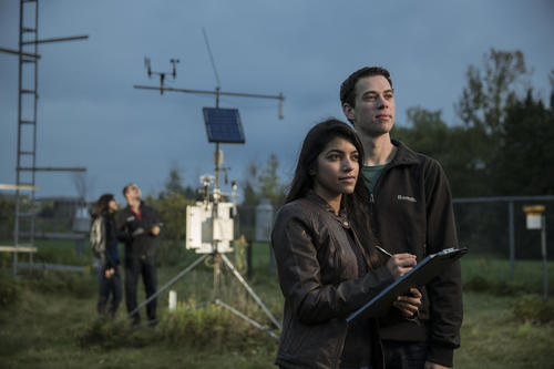 Two students standing outside with a weather station behind them.
