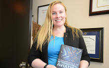 Dr. Suzanne Kearns holds her new book and smiles at the camera