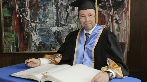 Dean Roy wearing academic regalia while signing register