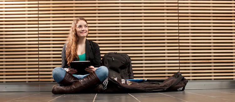 Picture of an undergrad student sitting cross-legged with a tablet and her backpack