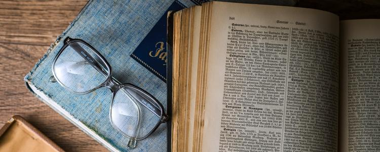 Picture of an open german encyclopedia on top of another, closed book and next to a pair of glasses