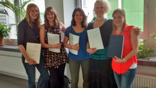 Five happy students hand in their MA theses.