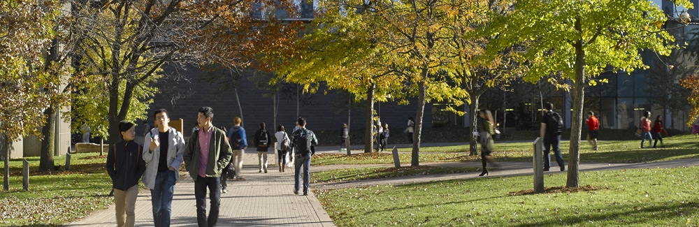 Students walking between MC, QNC, and SLC in autumn