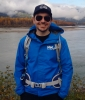 Max Salman by a lake wearing a blue jacket and sunglasses.