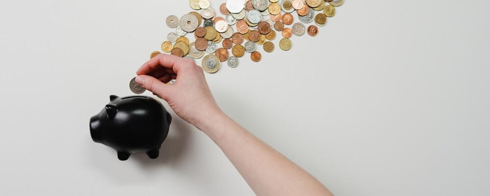 Black piggy bank with hand placing coins in the bank