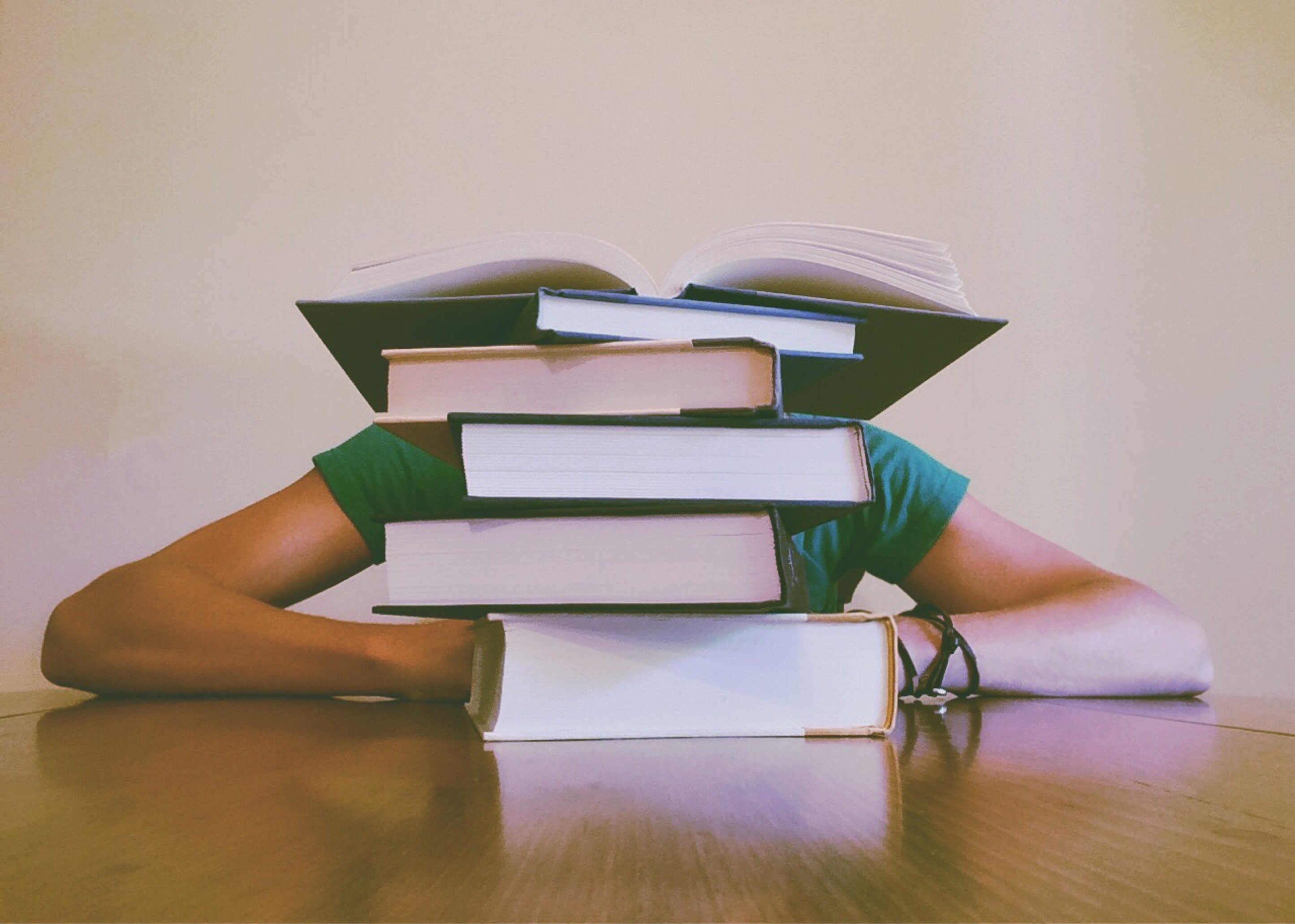 student behind pile of book