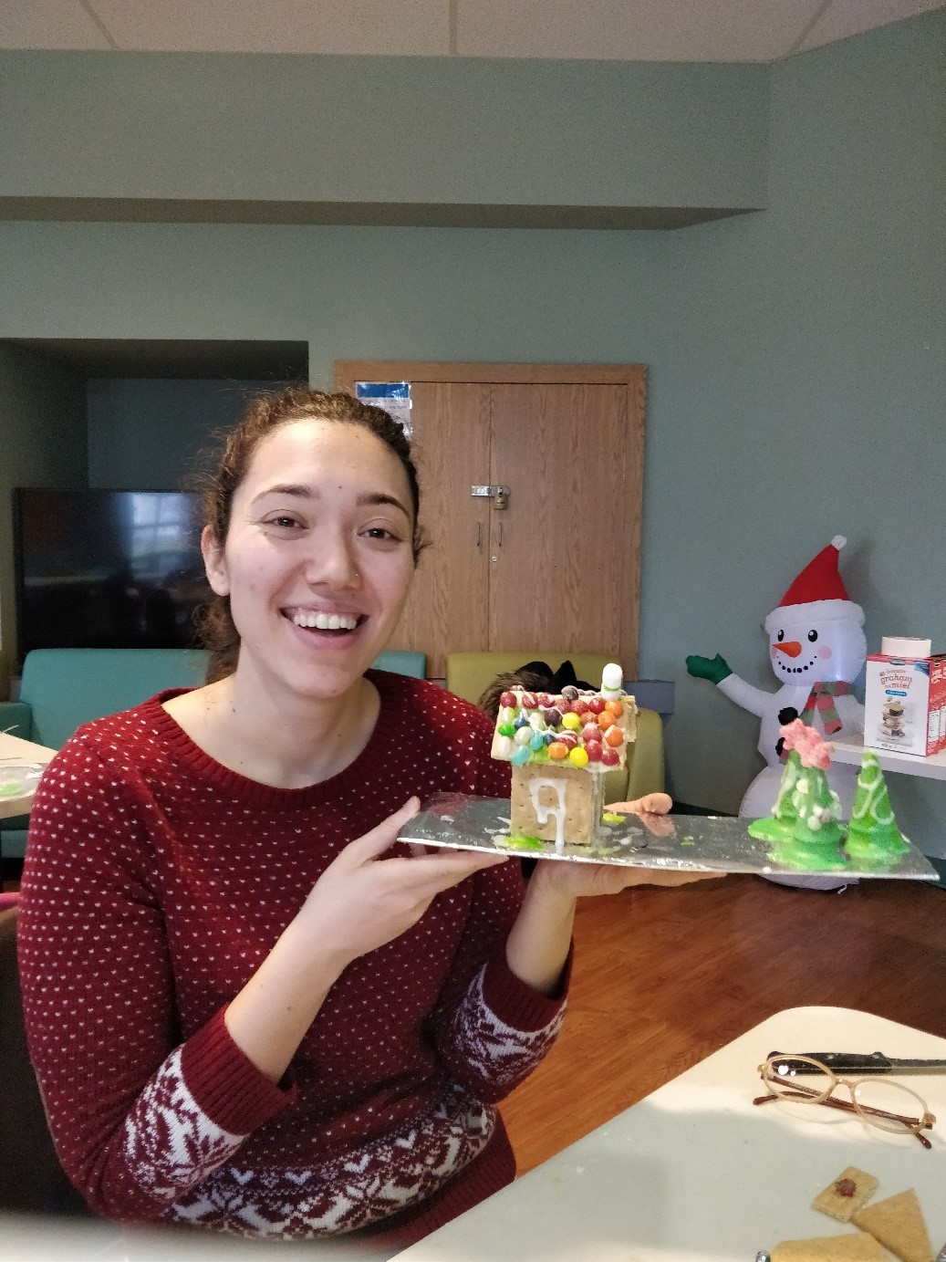 Ekin Eray holds a gingerbread house made during a community event.