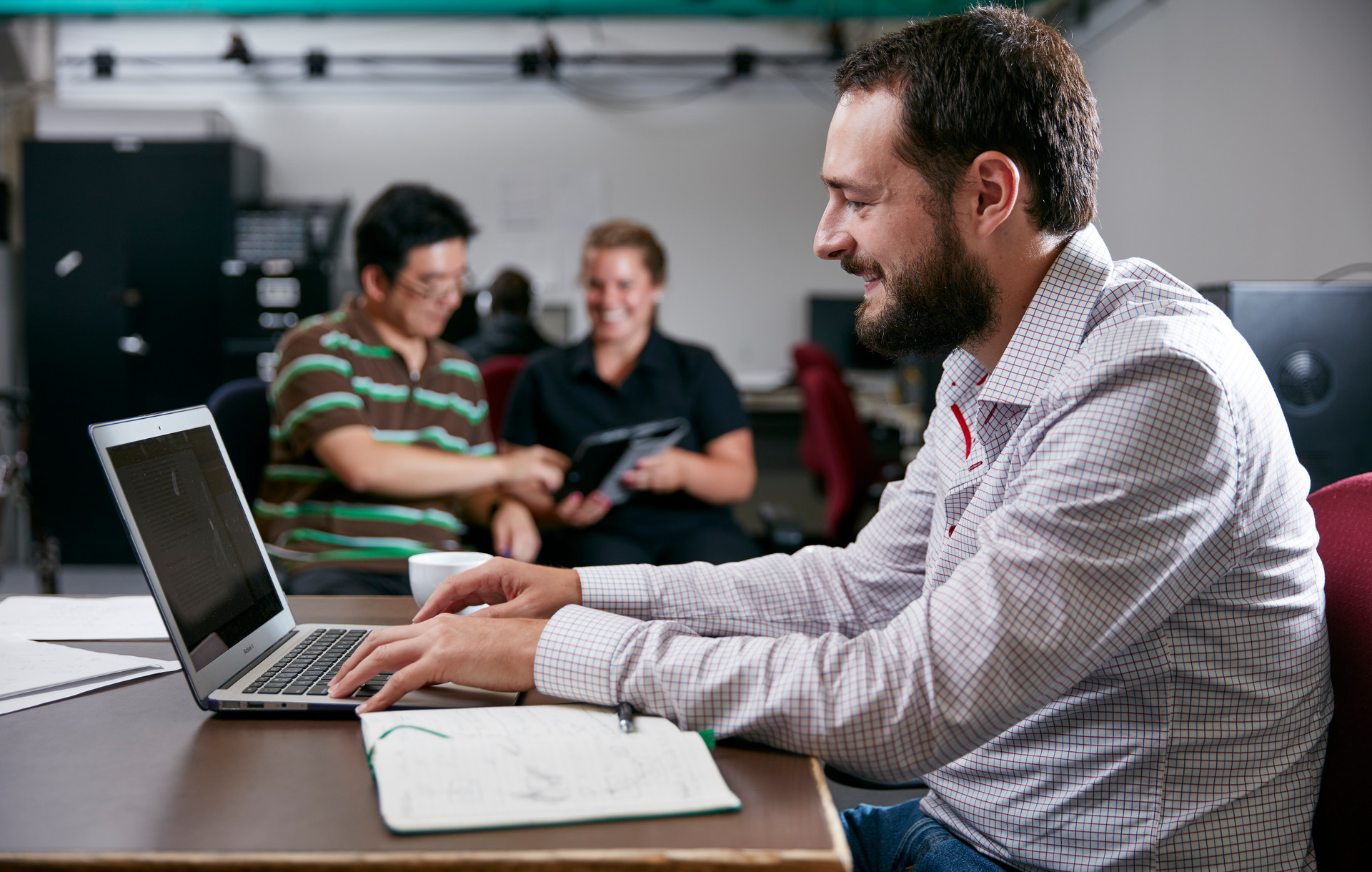 Male student working at desk on computer