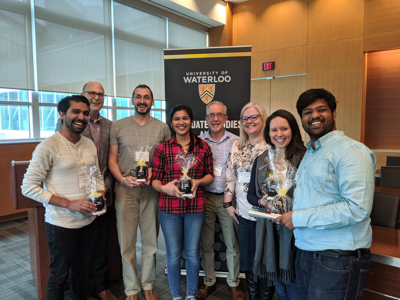 PhD Candidates holding mug