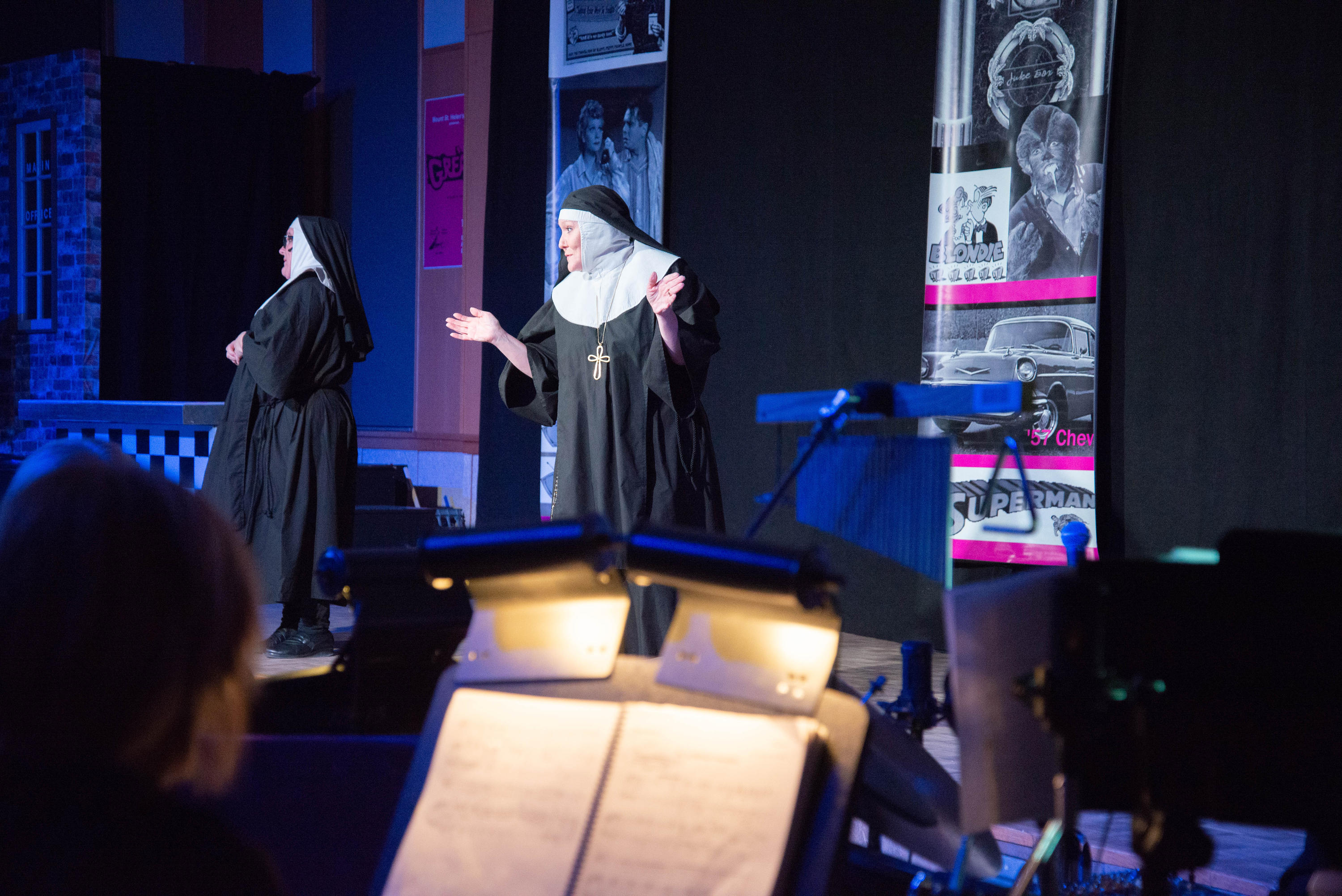 A nun sings on stage with a musician in the foreground