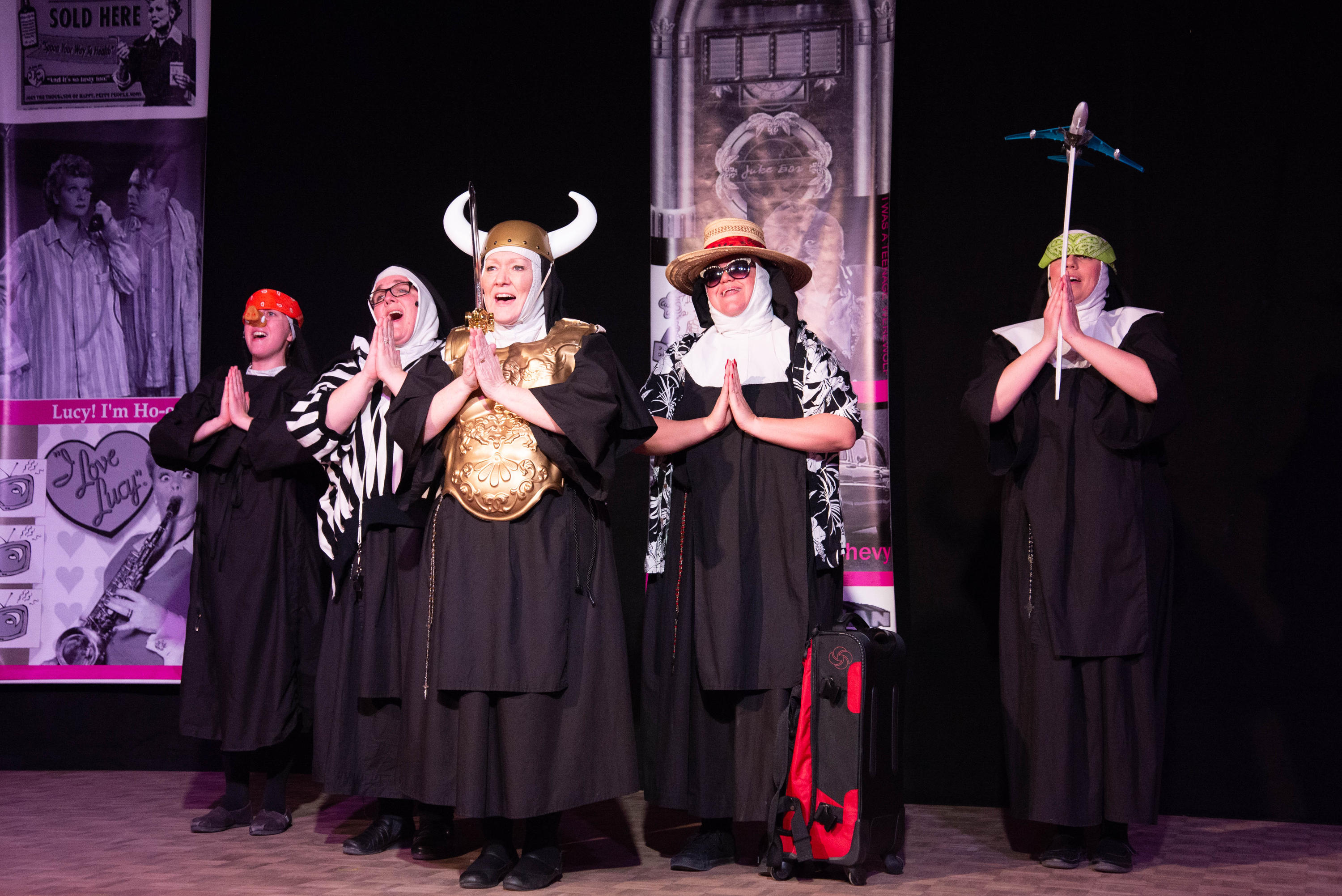 A group of actresses dressed as nuns sing on stage with props like viking horns, a model airplane, and traveling gear.