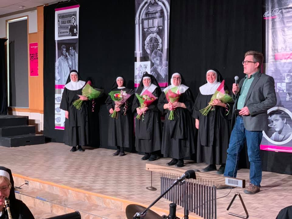 The cast of Nunsense holds flowers and are thanked by president Marcus Shantz