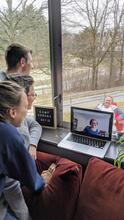 Students in the apartments meet with student services through a window and laptop during covid 19