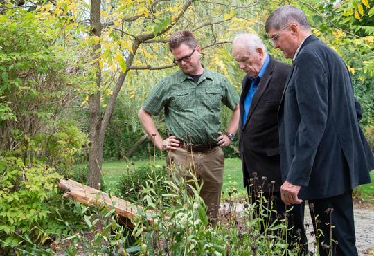 Marcus Shantz, John Ruth, and Wilmer Martin ponder the revised plaque in Grebel's Swiss Mennonite Heritage Garden.
