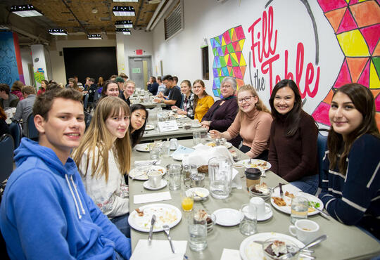 Students sit at a table for community supper