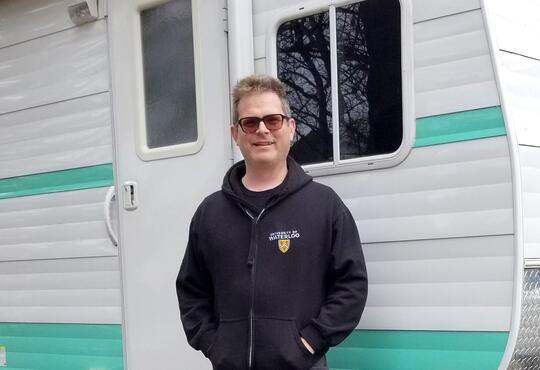 Grebel president Marcus Shantz stands outside of a white and blue camping trailer.