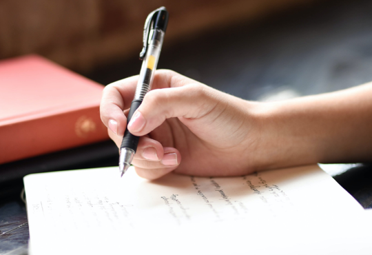 hand writing with a pen in a journal