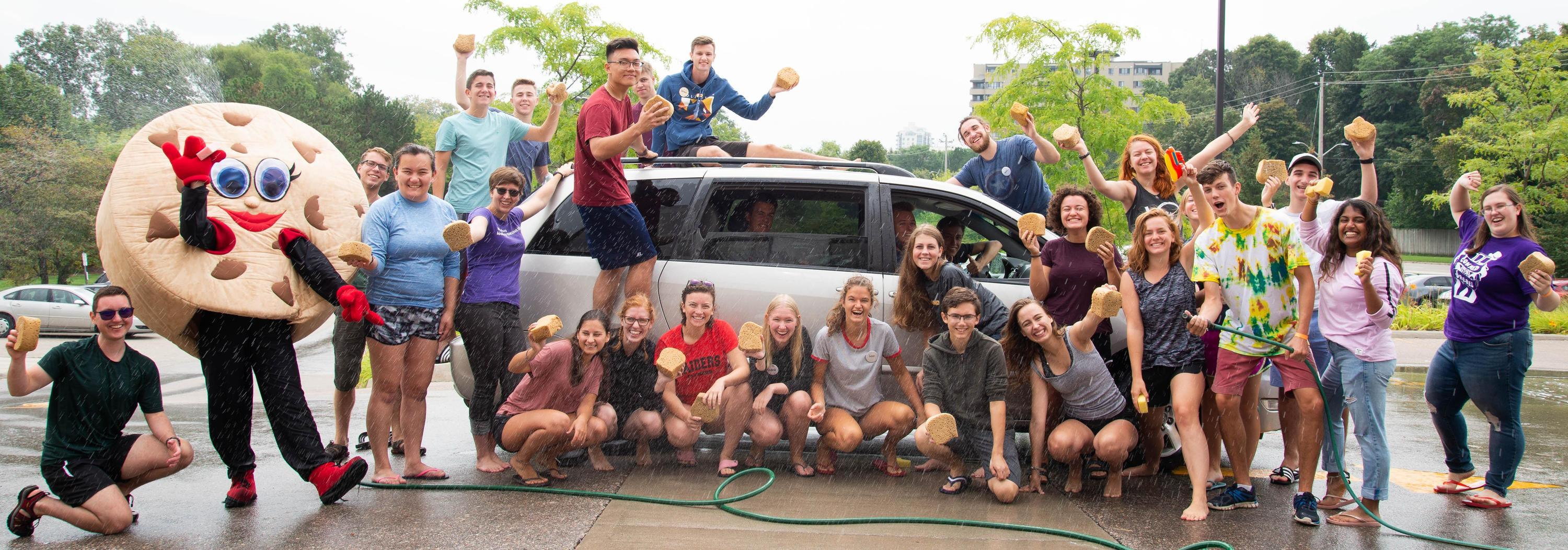 Upper-year students washing a car at the free car wash that they held during Orientation Week.