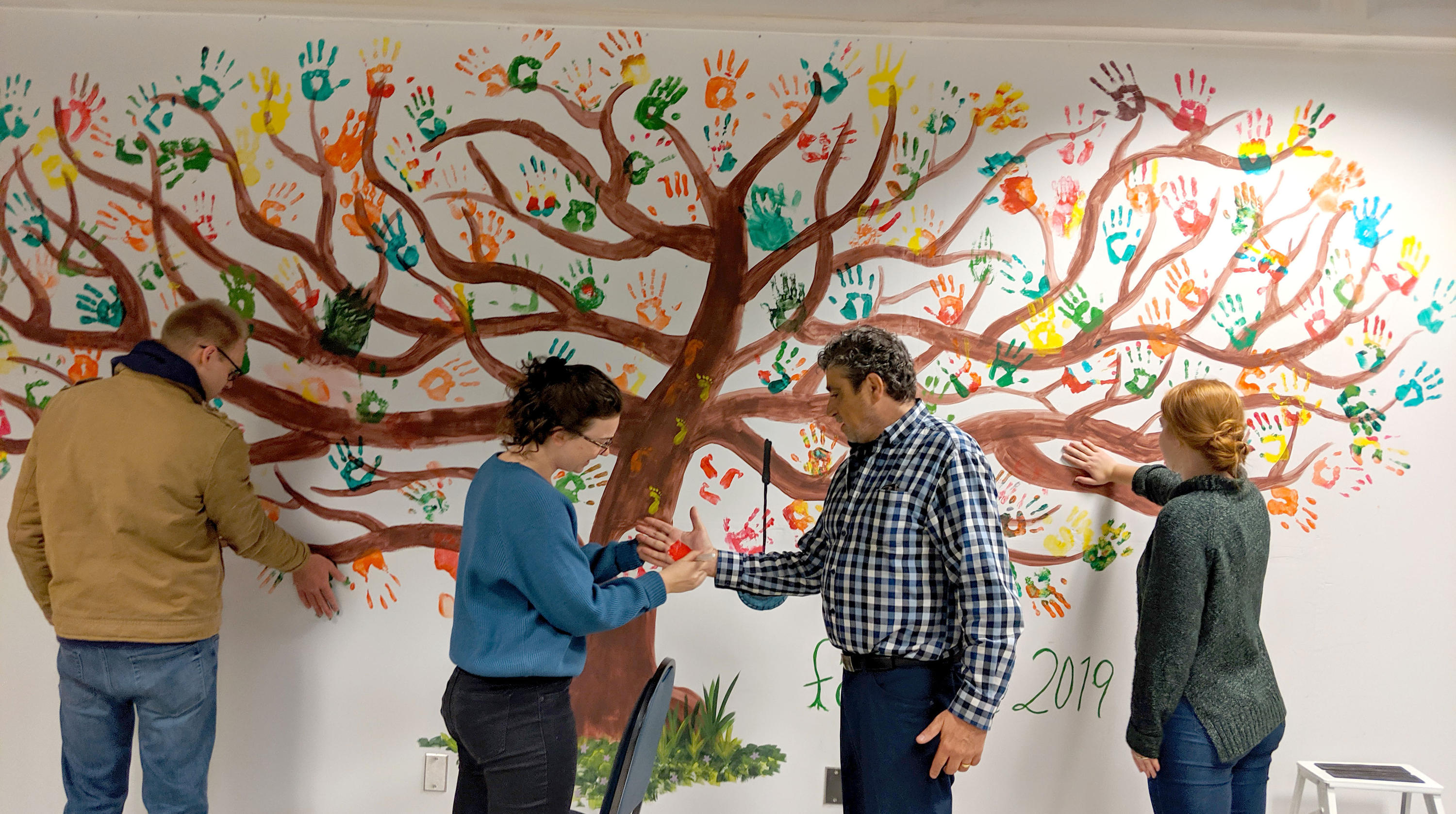 Staff and students adding their handprints to the painted tree in the dining room