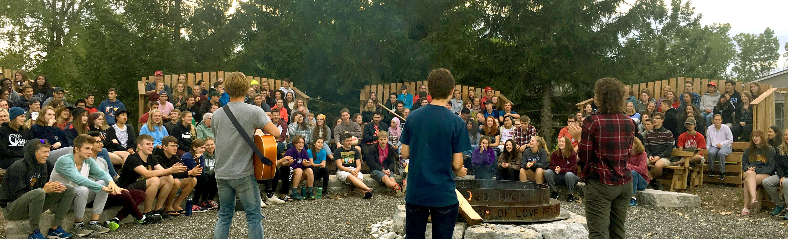 Students gathered around a campfire at the annual All-College Retreat