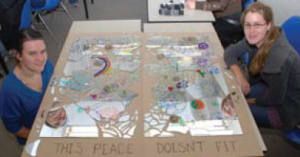 """This peace doesn't fit"" project with the 2 students who created it."