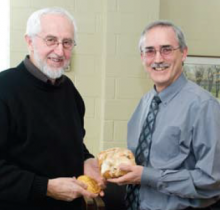 At a small Grebel celebration, Ernie Regehr stands with his Pearson Peace Medal as Henry Paetkau presents him with Grebel's own style of medal - a massive cinnamon bun!