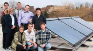 A group photo of Solar Grebel with the solar panels beside them.