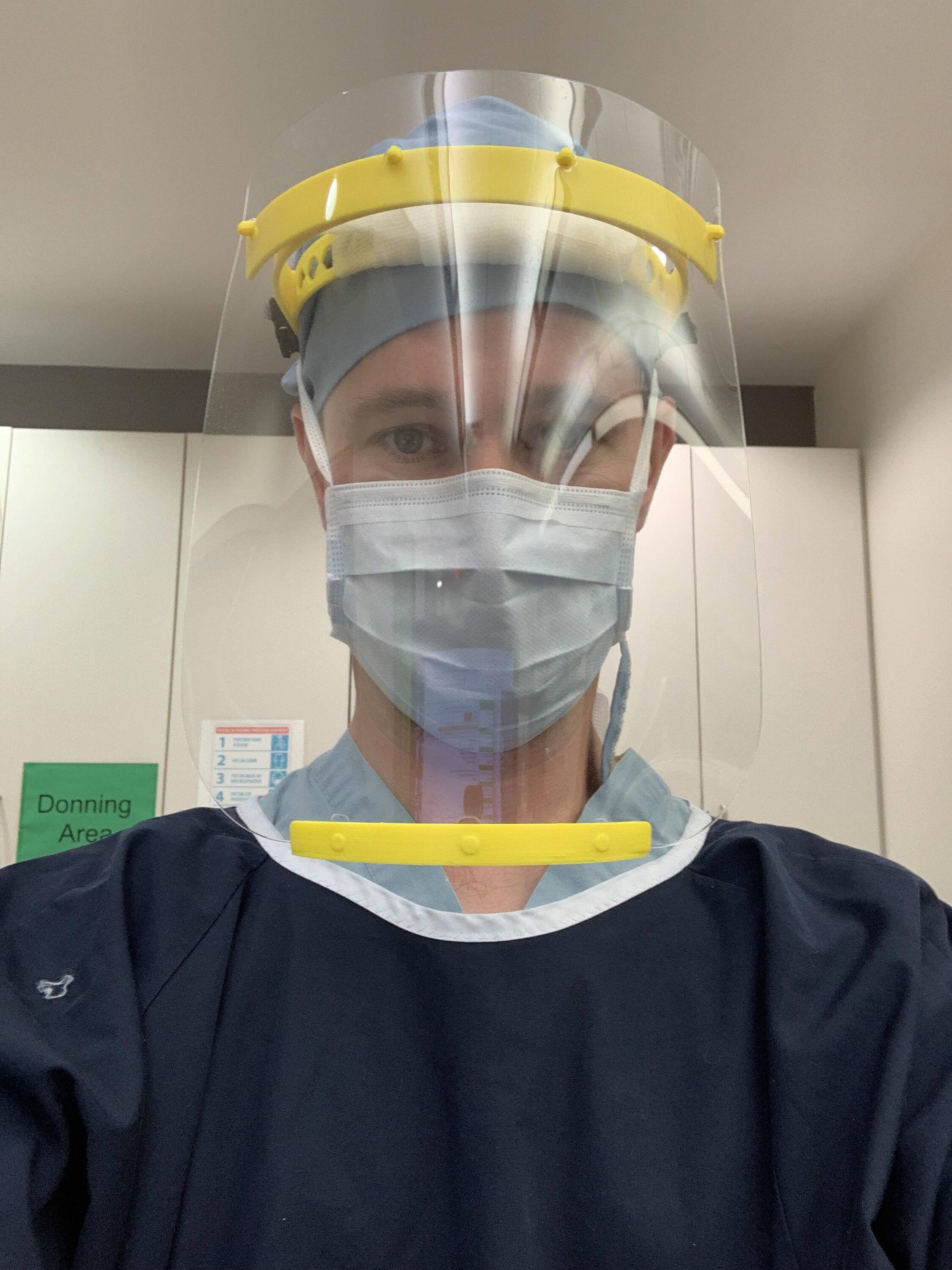 Art Winter takes a photo of himself wearing a full face shielf and mask in his hospital setting.