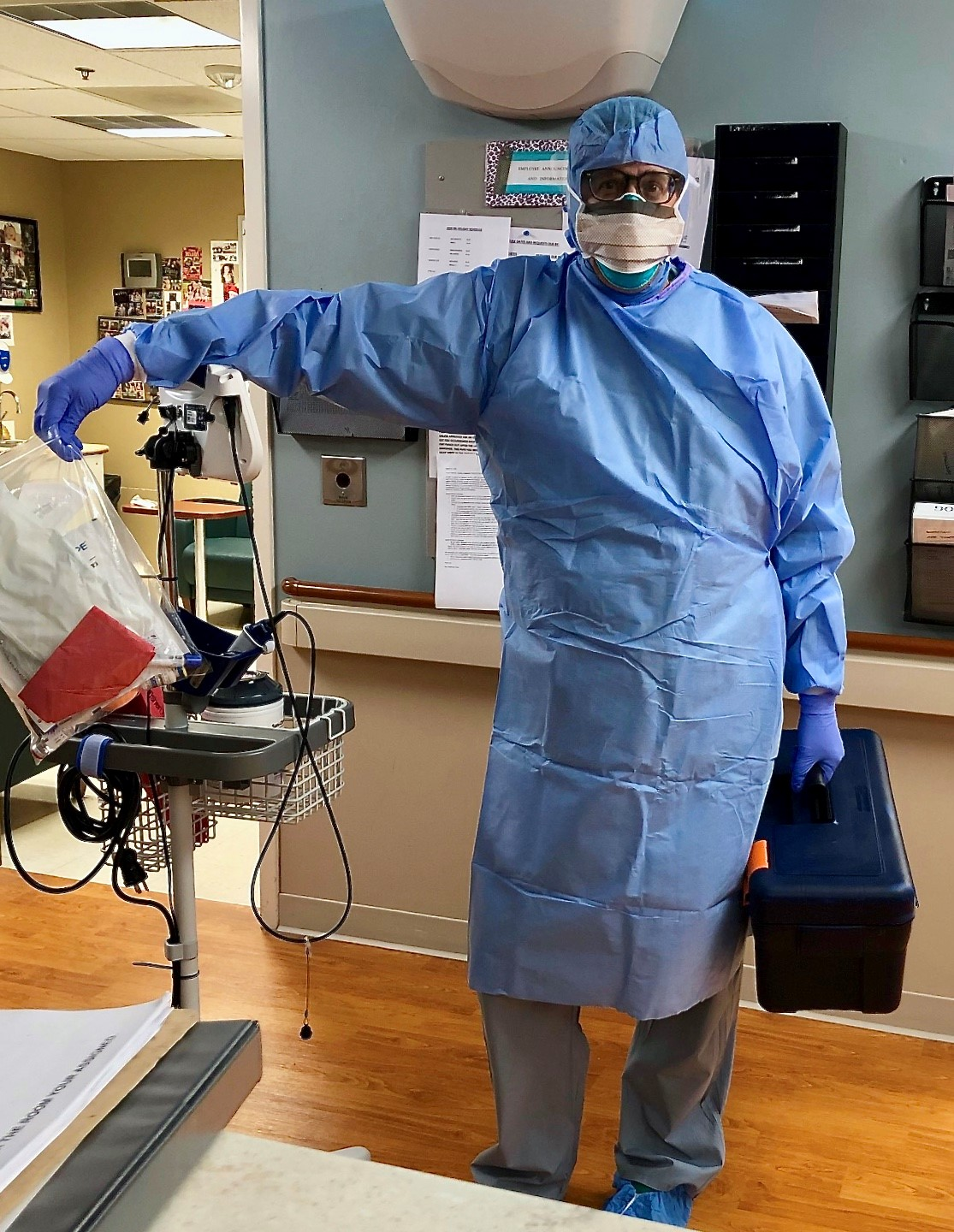 Mike stands with a videoscope station and holds a toolbox while dressed in protective equipment. He is about to assess a patient with suspected COVID-19
