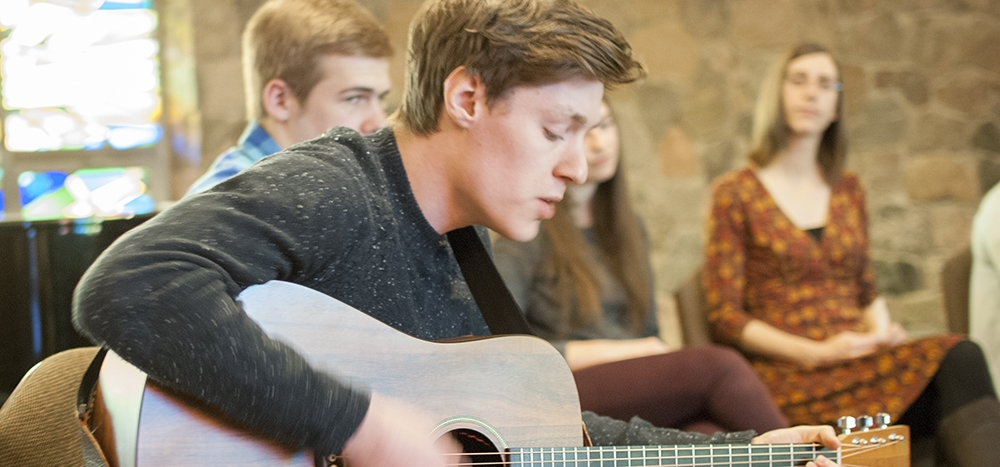 student playing guitar in chapel