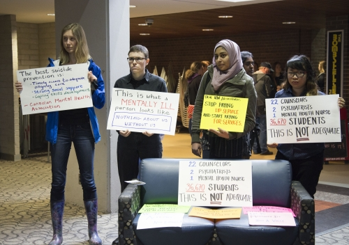 UWaterloo students hold signs to raise mental-health awareness.