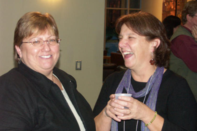 Two women talking, one is holding a coffee cup and laughing at what the other woman is saying.