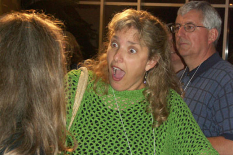 A woman in a green poncho who is very excited to see someone she knows