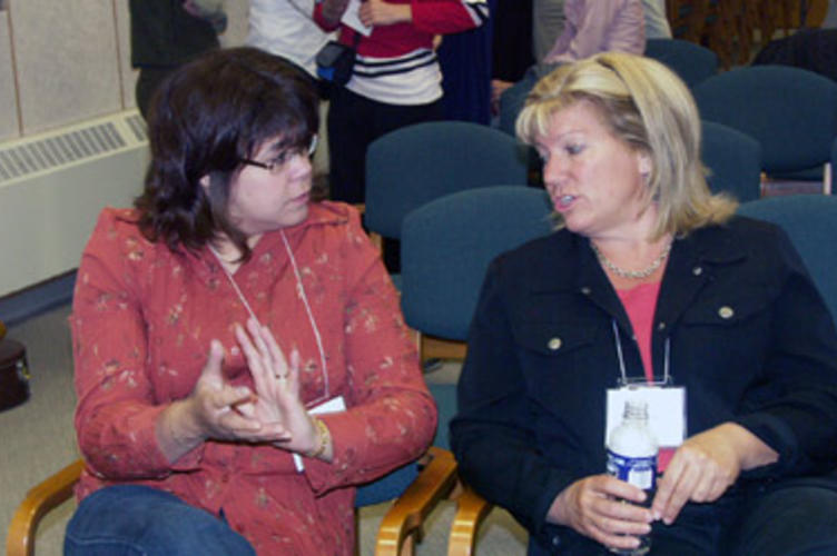 Two women talking in the auditorium