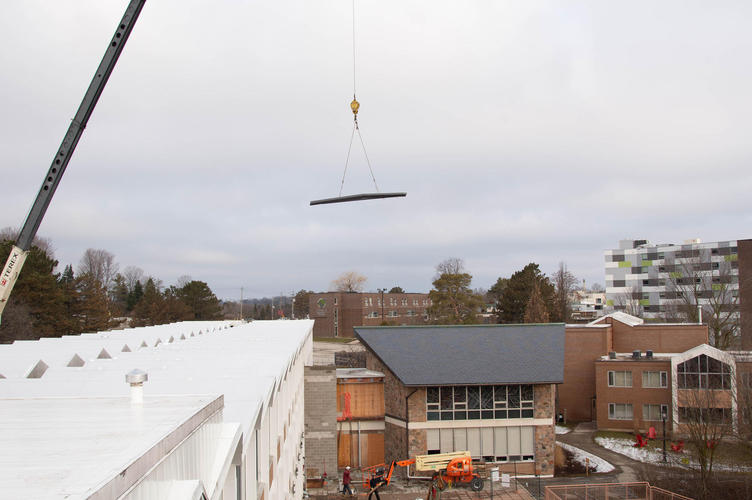 A crane towers over the residence building, carrying steal beams to the patio