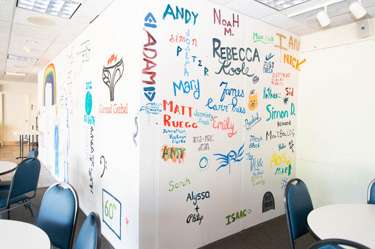 Summer students painted their names and faculty related images to a temporary wall in the cafeteria