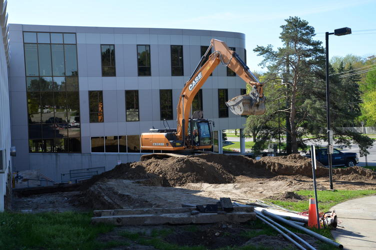 A backhoe begins digging on a bright sunny day