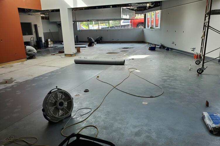 A construction crew begins installing the flooring in the new kitchen