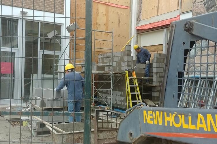 workers lay cinder blocks for the elevator shaft.