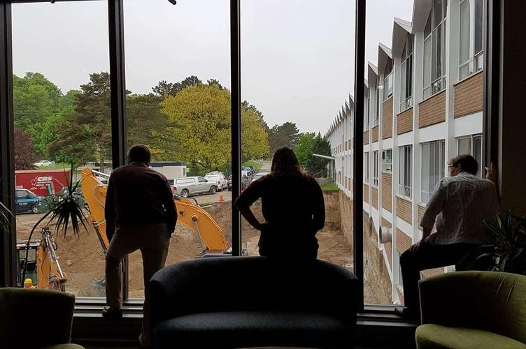 Staff watch construction progress from the library windows