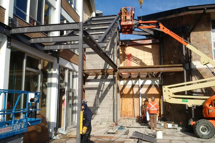 Steel beams are installed creating the structure for the new stairway on the patio