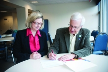 Susan Schultz Huxman and Ernie Ginsler sign the gift agreement.